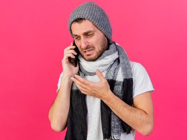 Das betrachten des traurigen jungen kranken mannes der seite, der wintermütze mit schal trägt, spricht am telefon lokalisiert auf rosa hintergrund