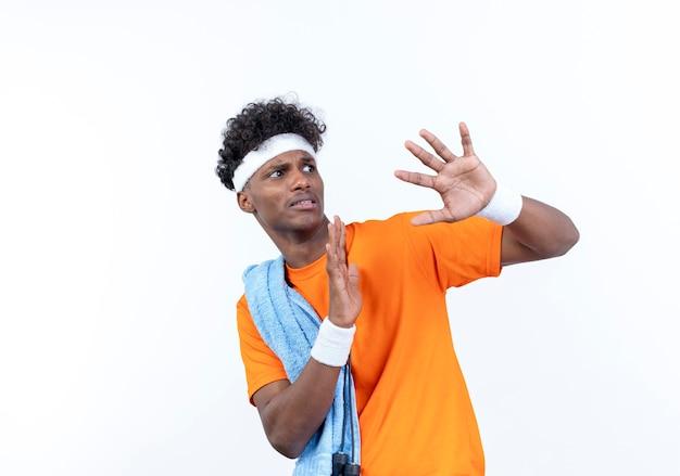 Das betrachten des verängstigten jungen afroamerikanischen sportlichen mannes der seite, der stirnband und armband trägt, spreizt hände mit handtuch auf schulter lokalisiert auf weißem hintergrund