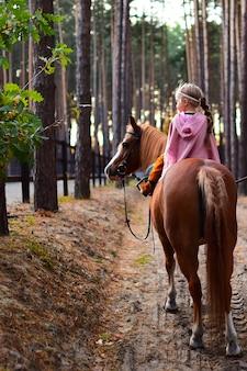 Das bezaubernde kleine mädchen, das wie eine prinzessin gekleidet wird, reitet ein pferd um den herbstwald