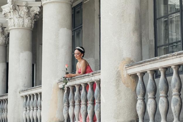 Das bezaubernde mädchen steht auf der ballcony