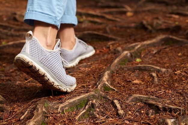 Das bild der frau graue turnschuhe und blaue hose tragend allein gehend in kiefernwald auf dem boden, frischluft und wunderbare landschaften genießend, legen das annoncieren von sportschuhen. reise- und beratungskonzept.