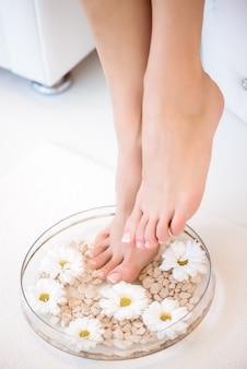Das bild der ideal gemachten maniküre und pediküre. weibliche beine im spa-spot.