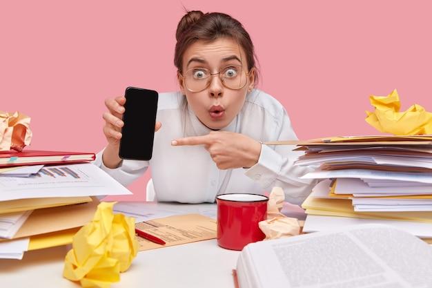 Das bild der schockierten jungen frau zeigt auf den scheinbildschirm des mobiltelefons, sieht mit verlegenem ausdruck aus, umgeben von dokumentation, posiert vor rosa hintergrund. reaktion