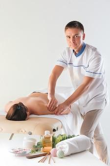 Das bild der schönen frau im massagesalon und in den männlichen händen auf ihrem körper