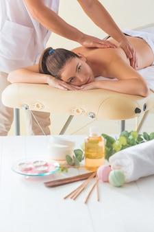 Das bild der schönen frau im massagesalon und in den männlichen händen schließen