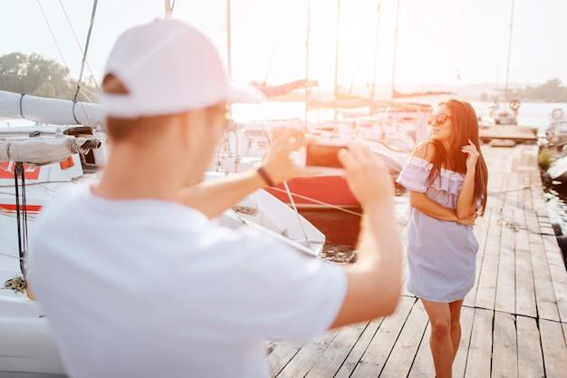 Das bild des jungen mannes steht auf dem pier und fotografiert die brünette.