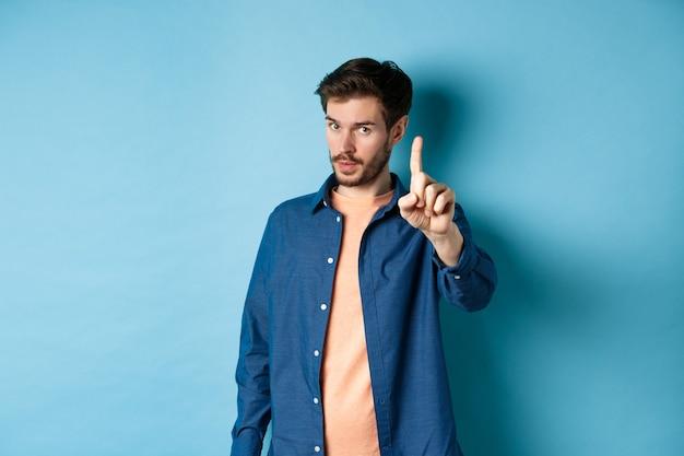 Das bild des jungen mannes warnt, lehrt eine lektion, hebt einen finger, um zu schelten, schaut in die kamera, bevormunden jemanden, der auf blauem hintergrund steht.