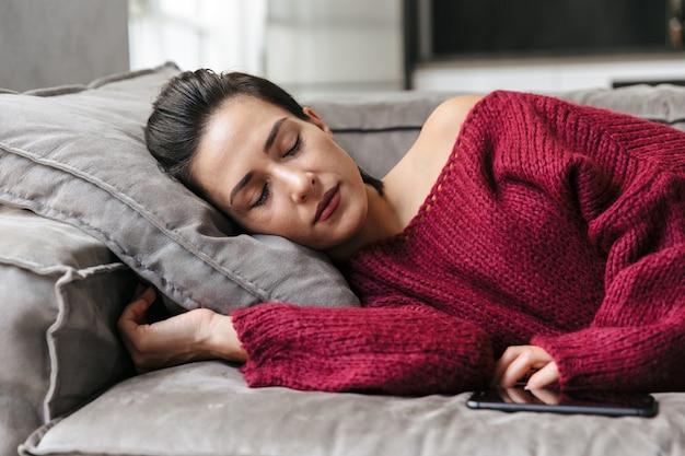 Das bild einer frau, die drinnen zu hause auf dem schlafsofa schläft, liegt eine pause.