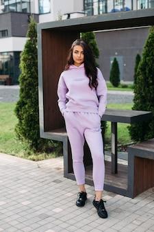 Das bild einer hübschen kaukasischen frau in einem lila sportanzug und schwarzen turnschuhen hält ihre hände in den taschen