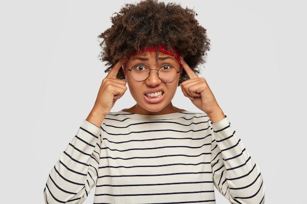 Das bild einer unzufriedenen, gestressten, dunkelhäutigen teenagerin hält beide zeigefinger an den schläfen