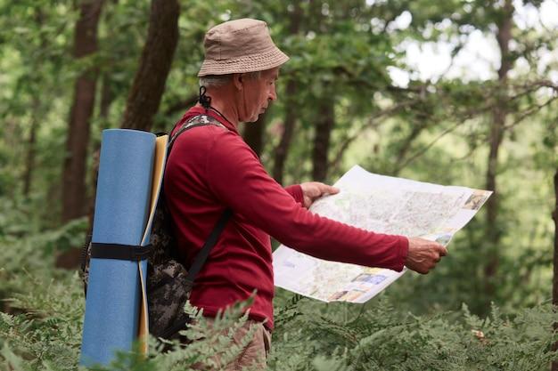 Das bild eines alten mannes, der reist, sich aktiv ausruht, seine berufung mit dem rucksack verbringt, mit der karte steht und versucht, den richtigen weg zu finden