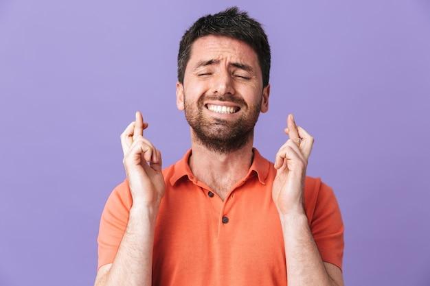 Das bild eines aufgeregten, nervösen, emotionalen jungen, gutaussehenden bärtigen mannes, der isoliert über einer violetten lila wand posiert, macht hoffnungsvolle geste.
