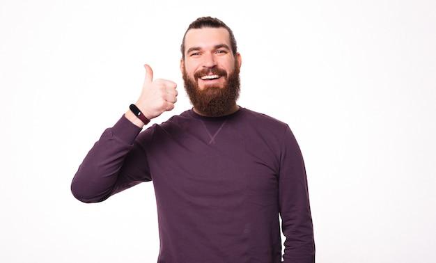 Das bild eines bärtigen jungen mannes lächelt in die kamera und zeigt einen daumen nach oben