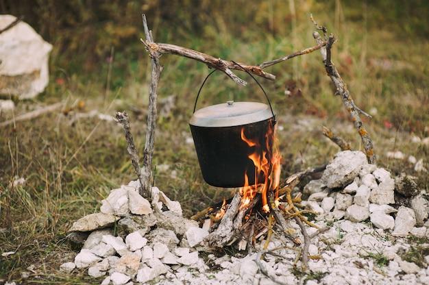 Das bild eines brandes in den wäldern, auf dem der topf gebraten wird