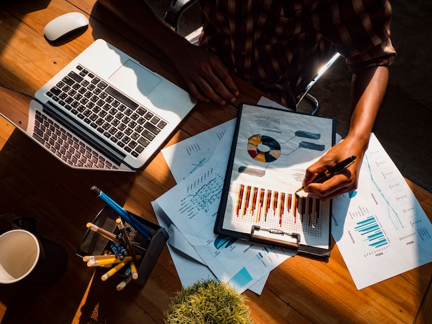 Das bild eines business-designers hält einen stift in der hand, um ein diagramm für ein erfolgreiches anlageergebnis zu schreiben.