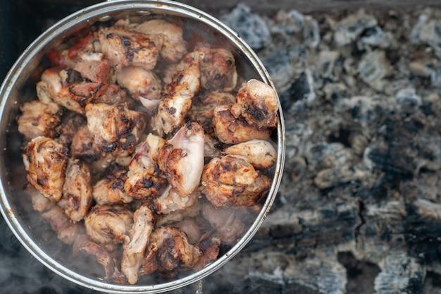 Das bild eines chiken-kebabs in einer großen pfanne befindet sich im winter in einem ausgestorbenen kohlenbecken