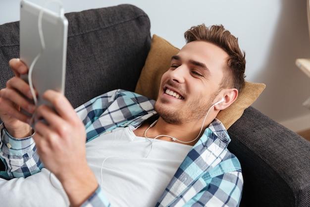 Das bild eines fröhlichen borstenmannes, der in einem hemd in einem käfigdruck gekleidet ist, liegt auf dem sofa zu hause und verwendet einen tablet-computer