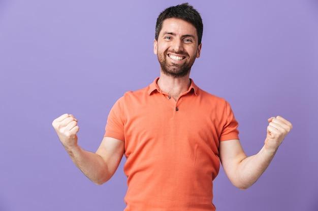 Das bild eines glücklichen jungen, gutaussehenden bärtigen mannes, der isoliert über einer violetten lila wand posiert, macht siegergeste.