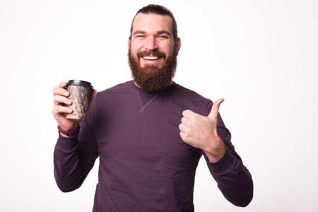 Das bild eines jungen bärtigen mannes lächelt in die kamera und zeigt mit einer tasse heißem getränk einen daumen nach oben