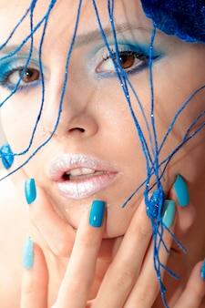 Das bild eines jungen mädchens mit blauem make-up und maniküre mit sandigem, glänzendem, buntem nageldesign mit glänzenden ornamenten auf dem kopf.