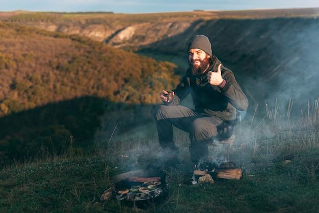 Das bild eines jungen mannes mit bart sitzt morgens in der nähe eines grills mit gemüse und würstchen auf einem feld