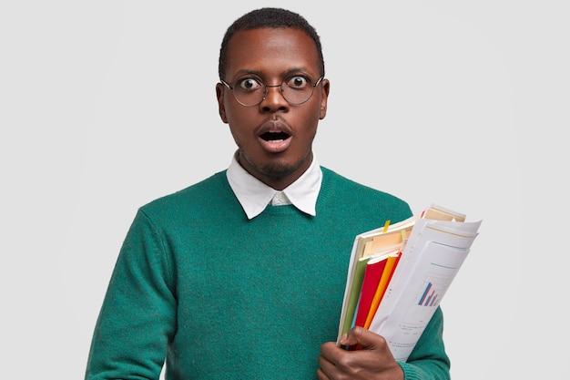 Das bild eines verblüfften männlichen angestellten hält papiere mit finanzbericht und diagrammen, wissenschaftliche literatur, bereitet sich auf geschäftsunterricht vor