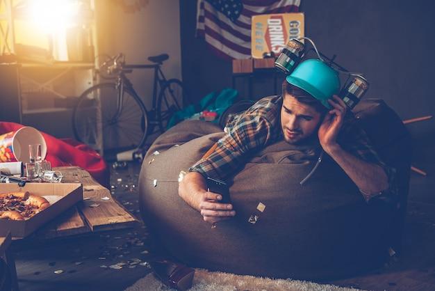 Das bild muss gelöscht werden! hübscher junger mann im bierhut mit seinem smartphone