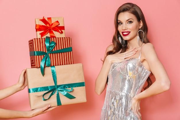 Das bild von jemandem gibt einer lächelnden, fröhlichen jungen frau in hellem paillettenkleid, isoliert über rosafarbener wand, ein geschenk.