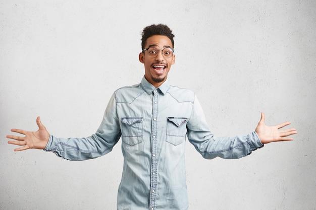 Das bild von talentierten männlichen angestellten zeigt aktiv, hat einen glücklichen und aufgeregten ausdruck, nachdem er bei der arbeit befördert wurde