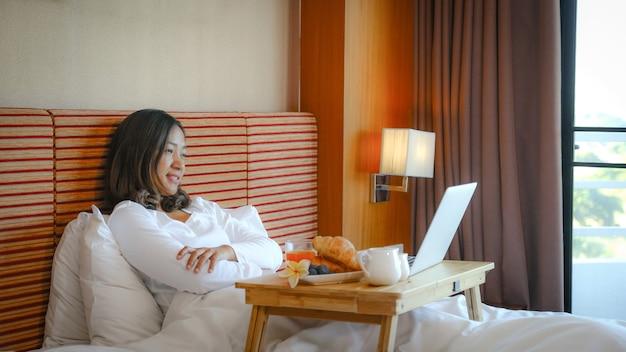 Das bild von touristen, die einen laptop benutzten und auf dem bett im luxushotelzimmer frühstückten