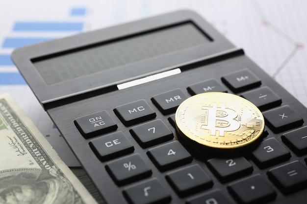 Das bitcoin liegt auf der tastatur des schwarzen taschenrechners gegen die große diagrammfinanzstatistik.