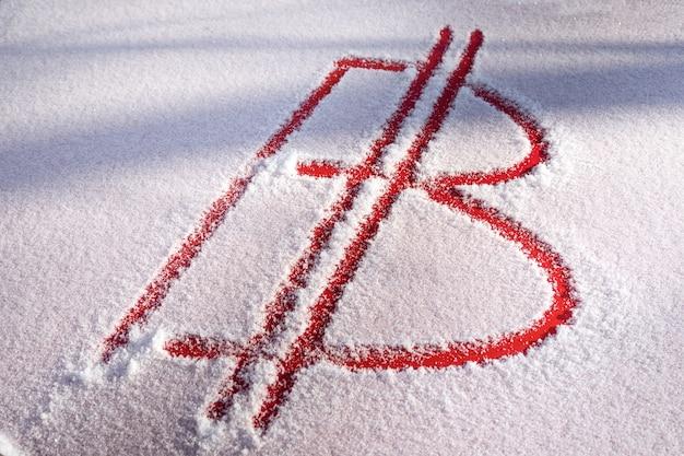 Das bitcoin-symbol ist im schnee handgeschrieben. rotes metall ist unter dem schnee sichtbar