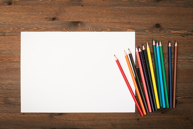 Das blatt ist rein weiß und buntstifte zum zeichnen auf einem hölzernen hintergrund mit einem platz zum kopieren. modell, modell, layout.