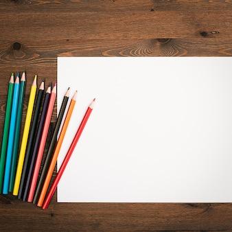 Das blatt ist rein weiß und buntstifte zum zeichnen auf einem hölzernen hintergrund mit einem platz zum kopieren.
