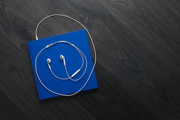 Das blaue buch und die weißen kopfhörer auf dem boden