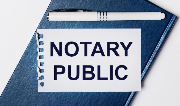 Das blaue tagebuch liegt auf hellem hintergrund. auf hat einen weißen stift und ein blatt papier mit dem text notary public.
