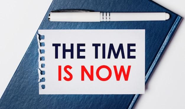Das blaue tagebuch liegt auf hellem hintergrund. on hat einen weißen stift und ein blatt papier mit dem text the time is now