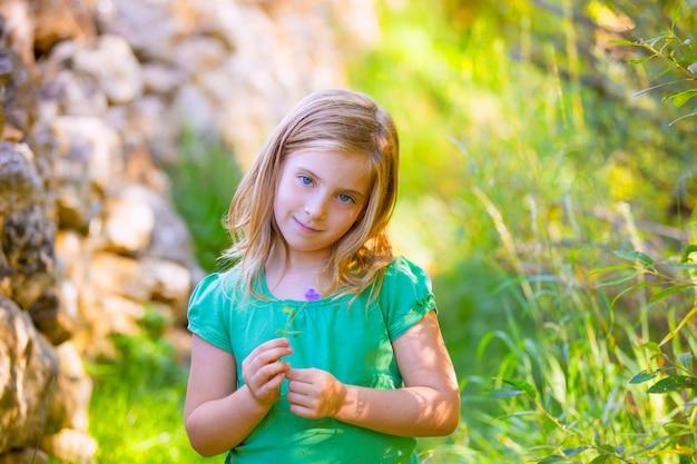 Das blonde kindermädchen, das mit purpurroter blume lächelt, entspannte sich im freien