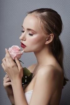 Das blonde mädchen, das rosafarbene blumen hält, nähern sich gesicht. schönheit