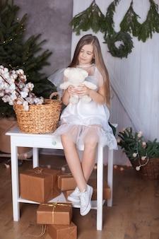 Das blonde mädchen in einem weißen kleid, das in einer umarmung mit einem teddybären sitzt. gemütliches zu hause. zimmer im öko-stil. weihnachtsstimmung, gemütlichkeit. nachdenkliches und verträumtes mädchen. ein haufen baumwolle auf dem tisch.