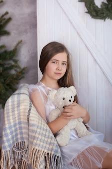 Das blonde mädchen in einem weißen kleid sitzt auf einem stuhl in einer umarmung mit einem teddybären und träumen. gemütliches zu hause. zimmer im öko-stil im einklang mit der natur. weihnachtsstimmung, gemütlichkeit.