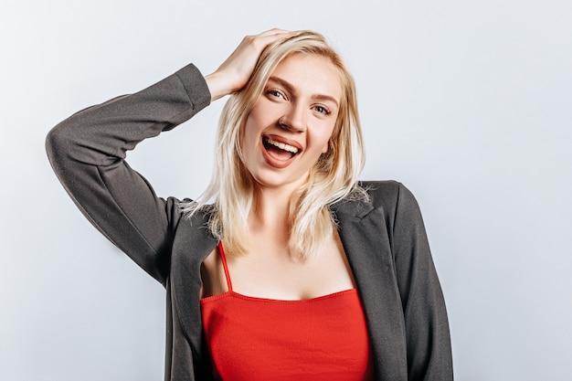 Das blonde mädchen ist glücklich und lächeln hält ihre hand an ihren kopf auf isoliertem hintergrund