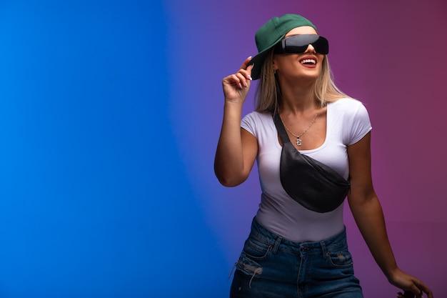 Das blonde model mit grüner mütze und sonnenbrille sieht positiv aus.