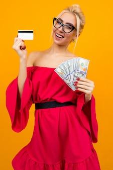 Das blonde sexy mädchen in einem roten kleid mit nackten schultern hält einen haufen kreditgeld und ein kreditkartenkreditmodell an einer isolierten wand