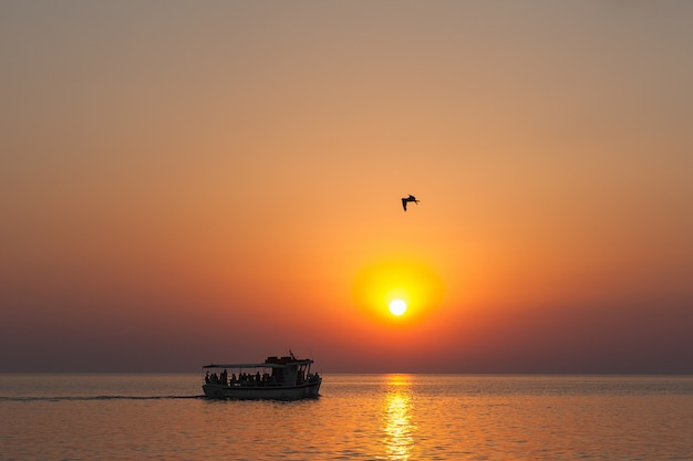 Das boot bei sonnenuntergang, mit touristen bei sonnenuntergang, schwimmt unter der sengenden sonne, einem fabelhaften seesonnenuntergang.