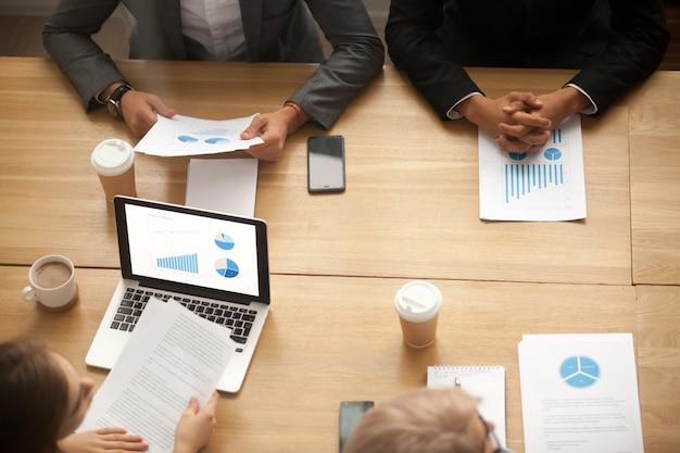 Das brainstorming des geschäftsteams, das statistiken analysiert, berichten bei der sitzung, draufsicht