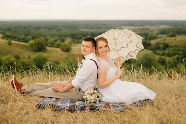 Das brautpaar beim picknick in der natur. braut und bräutigam nach der hochzeitszeremonie.