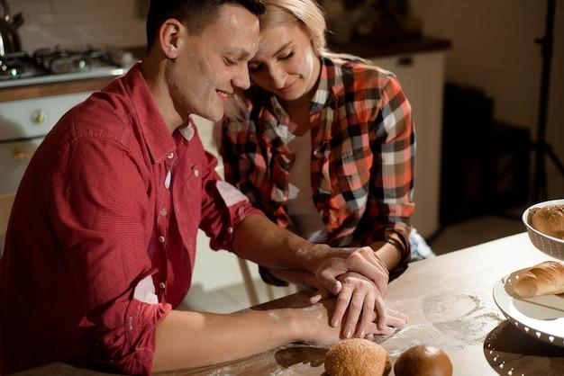 Das brautpaar bereitet am abend das abendessen zu und spielt mit mehl.