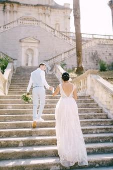 Das brautpaar steigt die treppe der geburtskirche der jungfrau maria kirche in prcanj hinauf