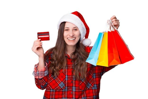Das breite lächelnde mädchen hält einige einkaufstüten, die sie zu weihnachten gekauft hat.